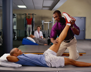Physical Therapist working wit ha patient.